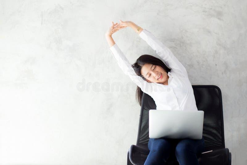 A mulher asiática nova bonita com estiramento do portátil e o exercício relaxam após o sucesso do trabalho fotografia de stock