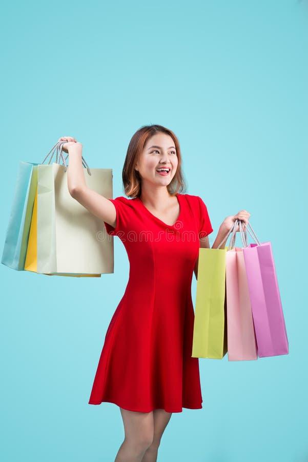 Mulher asiática nova bonita com os sacos de compras coloridos sobre o azul foto de stock royalty free