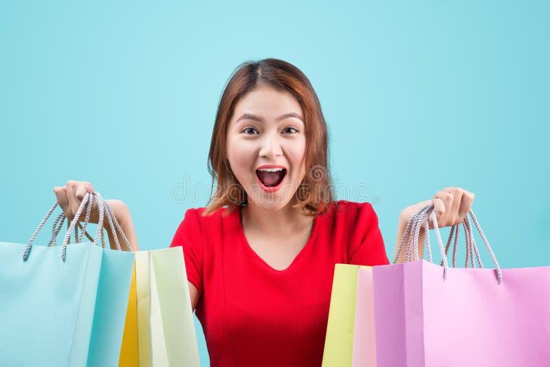 Mulher asiática nova bonita com os sacos de compras coloridos sobre o azul imagem de stock
