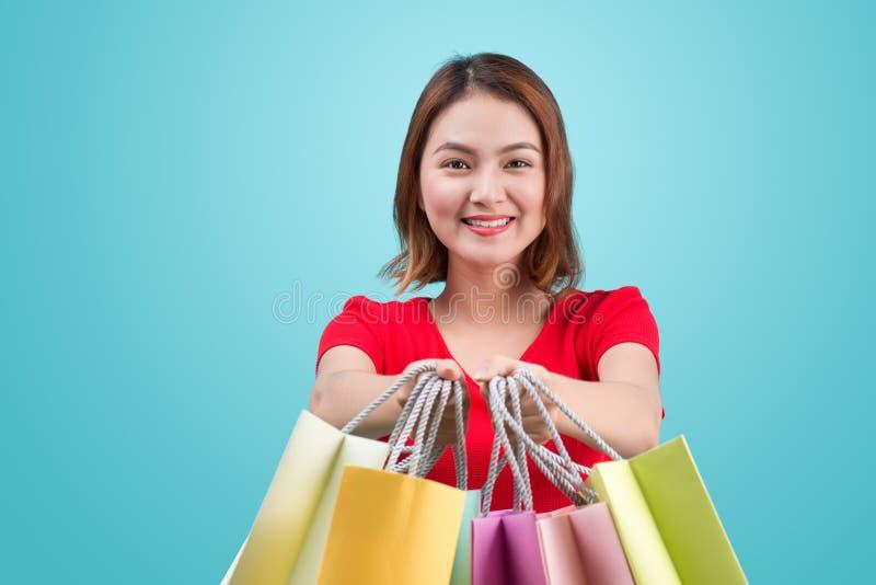 Mulher asiática nova bonita com os sacos de compras coloridos sobre o azul foto de stock