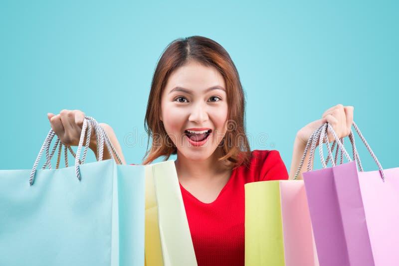 Mulher asiática nova bonita com os sacos de compras coloridos sobre o azul imagem de stock royalty free