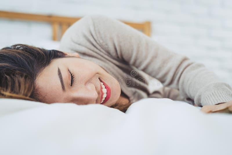 Mulher asiática nova bonita do retrato na cama em casa na manhã imagens de stock