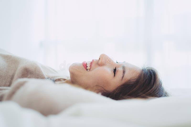 Mulher asiática nova bonita do retrato na cama em casa na manhã fotos de stock