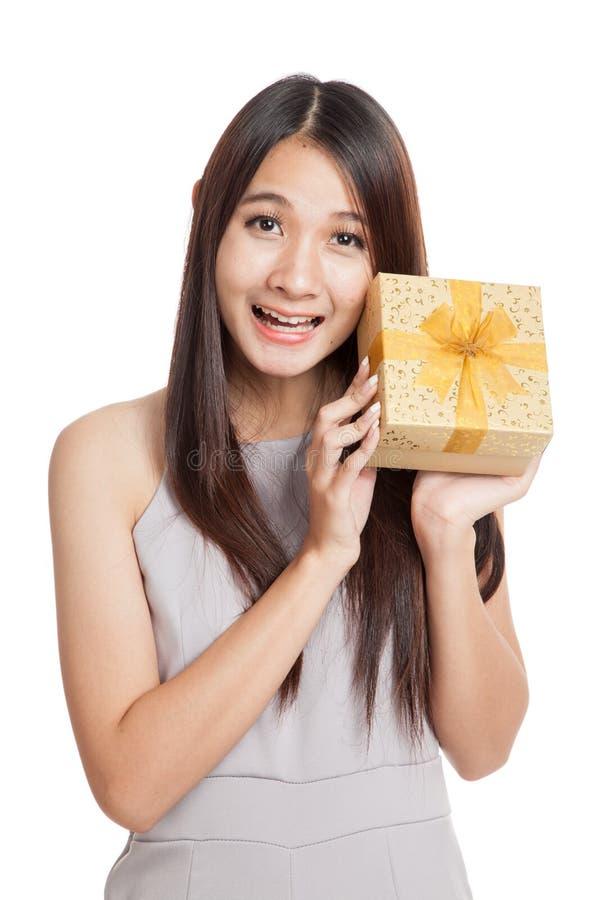 Mulher asiática nova bonita entusiasmado com caixa de presente dourada imagem de stock royalty free