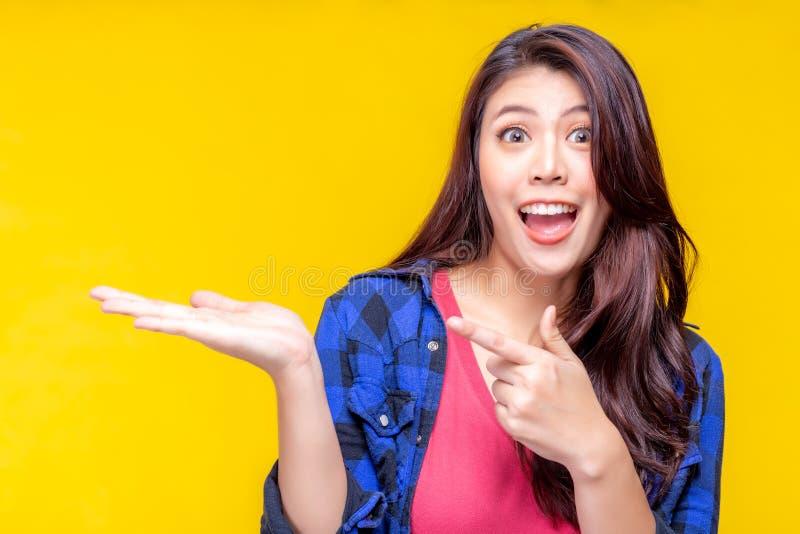 Mulher asiática nova bonita que aponta o dedo para copiar o espaço Produto bonito atrativo da mostra da menina que faz sua satisf fotografia de stock royalty free