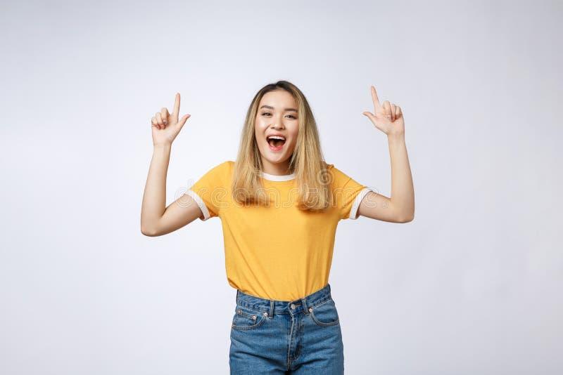 Mulher asiática nova bonita que aponta seu dedo acima com expressão alegre, no fundo branco imagens de stock royalty free