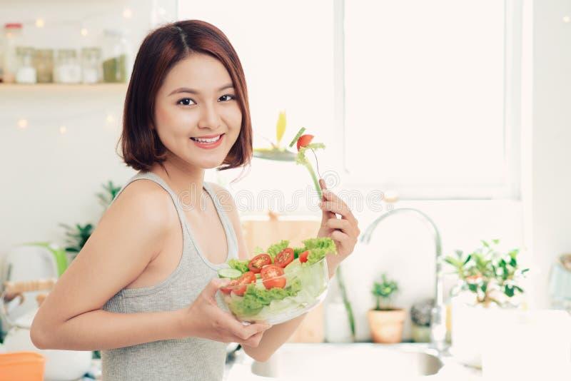 Mulher asiática nova bonita que come a salada do legume fresco Loosin fotos de stock