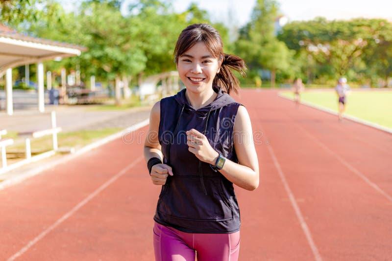 Mulher asiática nova bonita que exercita na manhã em uma pista de atletismo imagens de stock