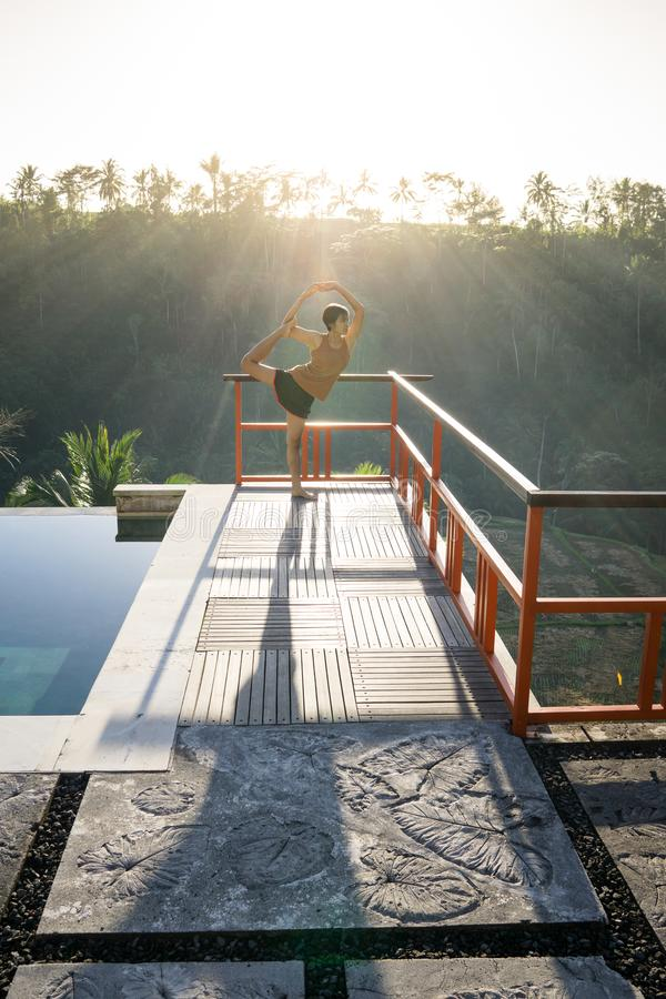 Mulher asiática nova bonita que faz o exercício da ioga com o Natarajasana que levanta o senhor da pose da dança perto da piscina imagem de stock