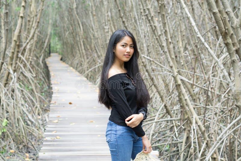Mulher asiática nova bonita que relaxa na ponte de madeira foto de stock