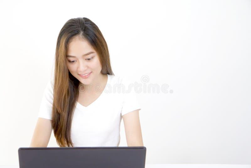 Mulher asiática nova bonita que senta-se na frente do laptop fotografia de stock