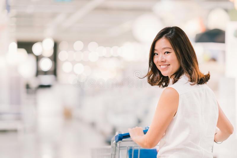 Mulher asiática nova bonita que sorri, com cena do carrinho de compras, do shopping ou do armazém, fundo do bokeh do borrão imagens de stock