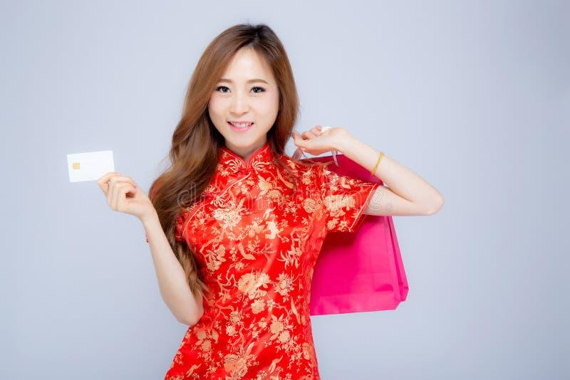 Mulher asiática nova chinesa feliz do retrato bonito do ano novo que guarda a exibição atual de compra do cartão do saco de papel imagem de stock royalty free