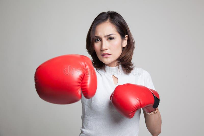 Mulher asiática nova com as luvas de encaixotamento vermelhas imagens de stock royalty free
