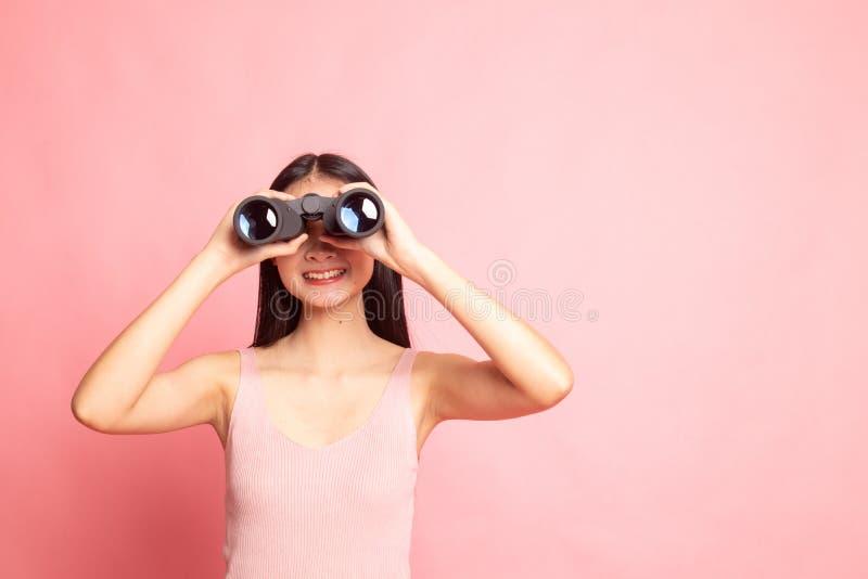 Mulher asiática nova com binóculos fotografia de stock royalty free