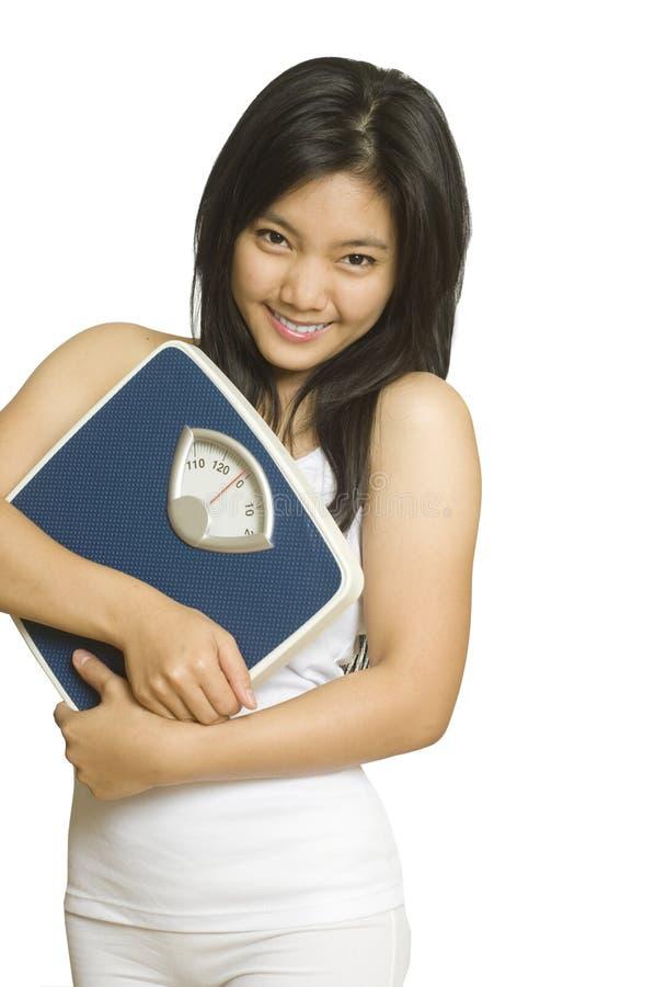 Mulher asiática nova com escala do peso fotografia de stock royalty free