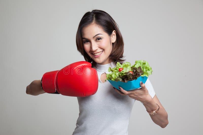 Mulher asiática nova com luva e salada de encaixotamento fotos de stock royalty free