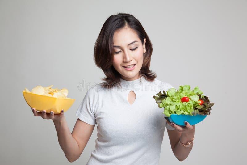 Mulher asiática nova com microplaquetas e salada de batata fotos de stock royalty free