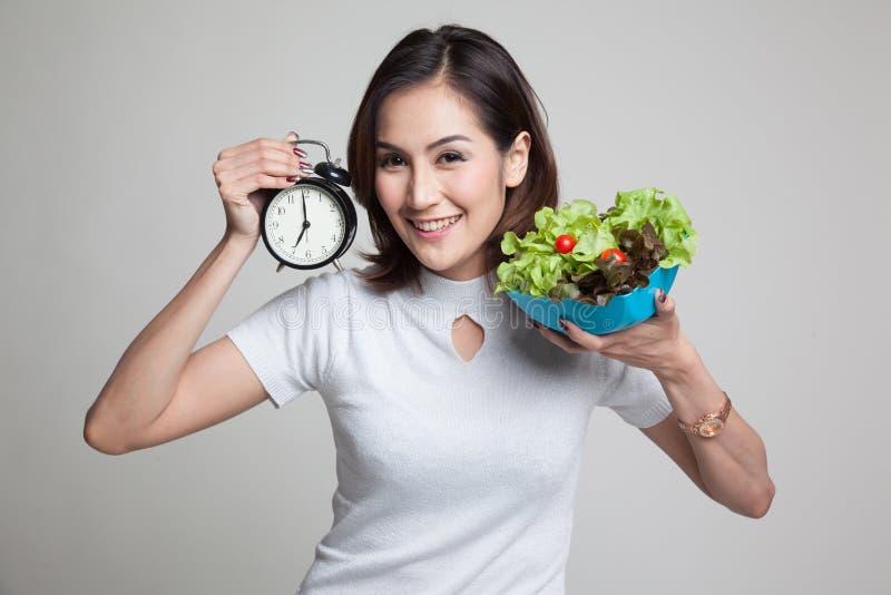 Mulher asiática nova com pulso de disparo e salada fotografia de stock