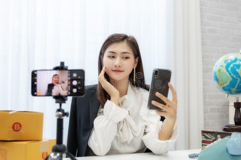 Mulher asiática nova como o vlogger ou blogger que atende à videoconferência imagens de stock