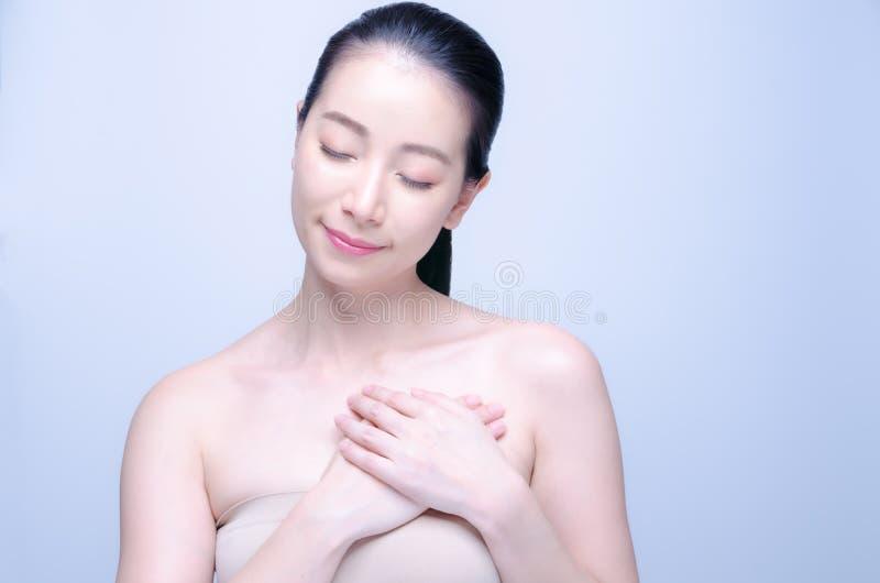 Mulher asiática nova da beleza que toca no coração saudável isolado no fundo azul Sentimentos e conceito do amor Dia do Valentim  imagens de stock