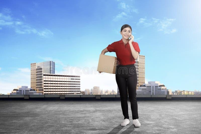 Mulher asiática nova da entrega com pacote que fala no telefone celular foto de stock