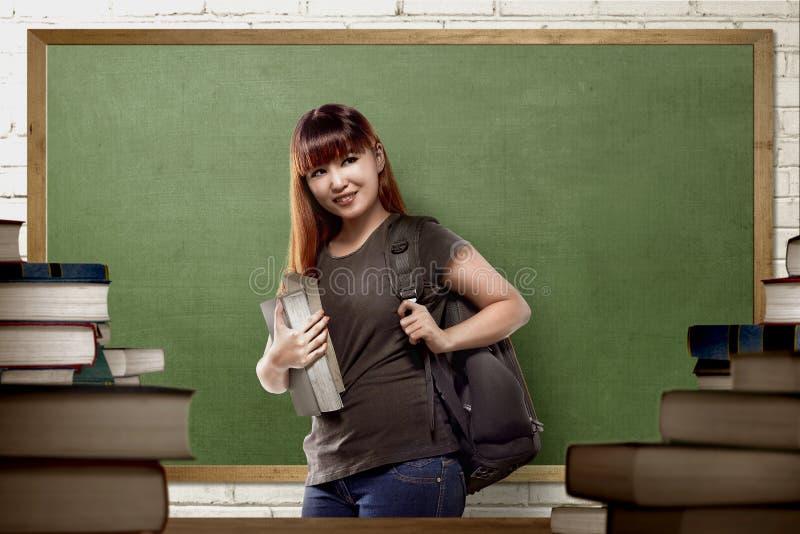 Mulher asiática nova da estudante universitário com trouxa imagem de stock royalty free