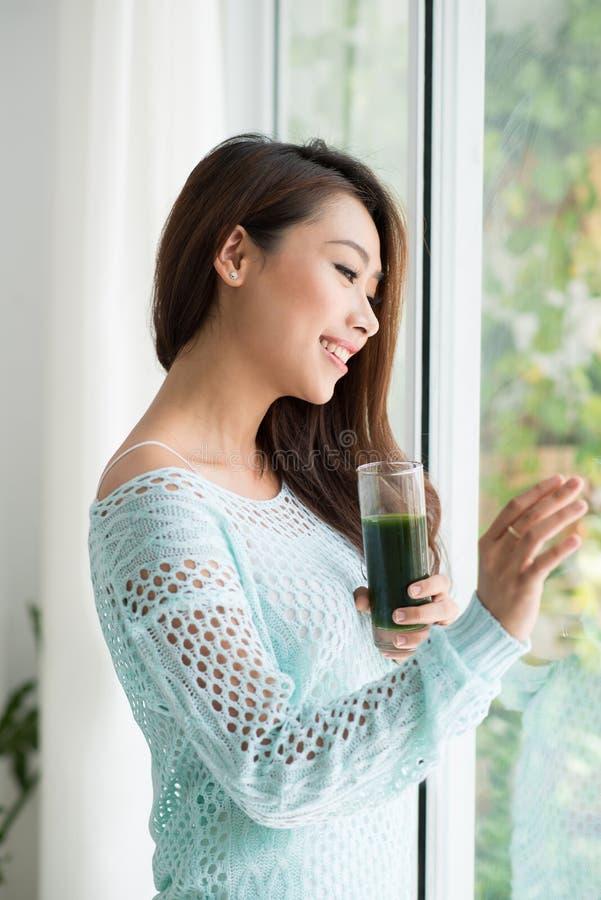 Mulher asiática nova de sorriso que bebe o suco verde o do legume fresco imagens de stock