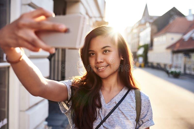 Mulher asiática nova de sorriso que toma selfies em uma rua da cidade fotos de stock