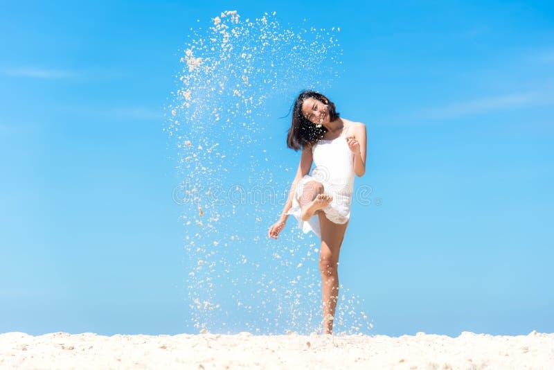 A mulher asiática nova do estilo de vida relaxa a areia do pontapé e o salto na praia bonita fotografia de stock