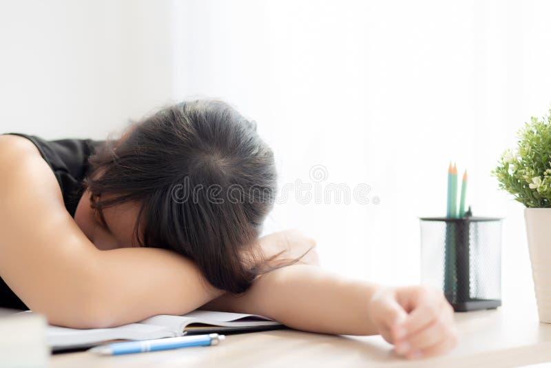 Mulher asiática nova do retrato bonito que aprende o exame ou os trabalhos de casa e o sono com cansado e esforço fotos de stock royalty free