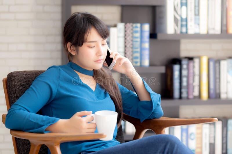 A mulher asiática nova do retrato bonito que sorri usando o telefone esperto móvel que fala para apreciar e beber o café com rela imagem de stock royalty free