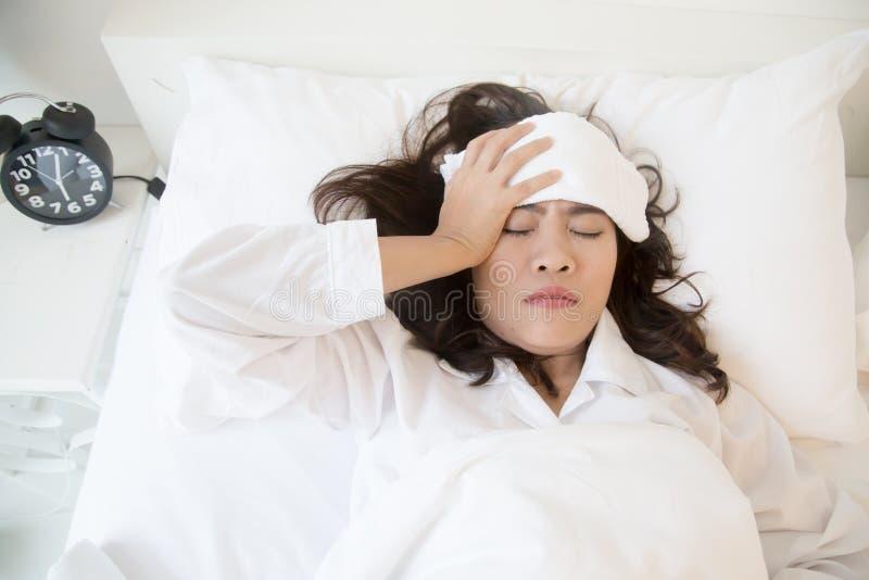 Mulher asiática nova doente que encontra-se na cama imagem de stock royalty free
