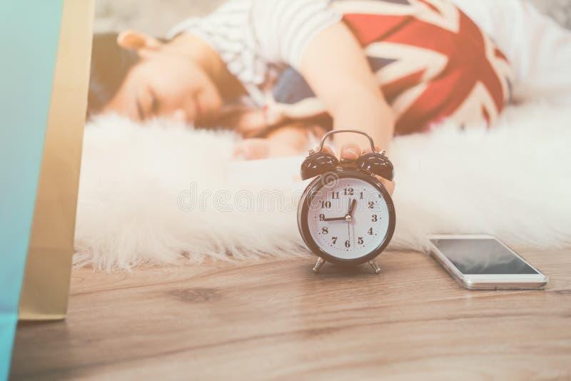 Mulher asiática nova feliz que acorda e que gira fora o despertador imagens de stock royalty free