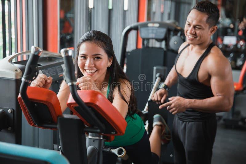 A mulher asiática nova feliz que faz o pé traseiro pressiona fotografia de stock