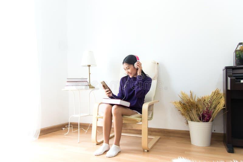A mulher asiática nova inspirada que escuta a música em casa, relaxa e vida feliz imagem de stock royalty free