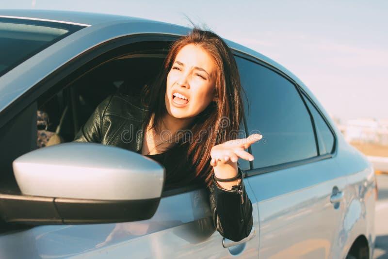 Mulher asiática nova irritada do cabelo longo moreno bonito que conduz e que grita no carro imagem de stock