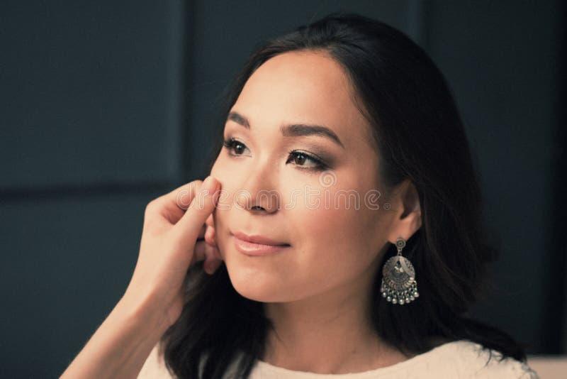 Mulher asiática nova limpe a pele que descansa após o skincare, no fundo escuro cara fresca perfeita dos termas bonitos imagens de stock royalty free