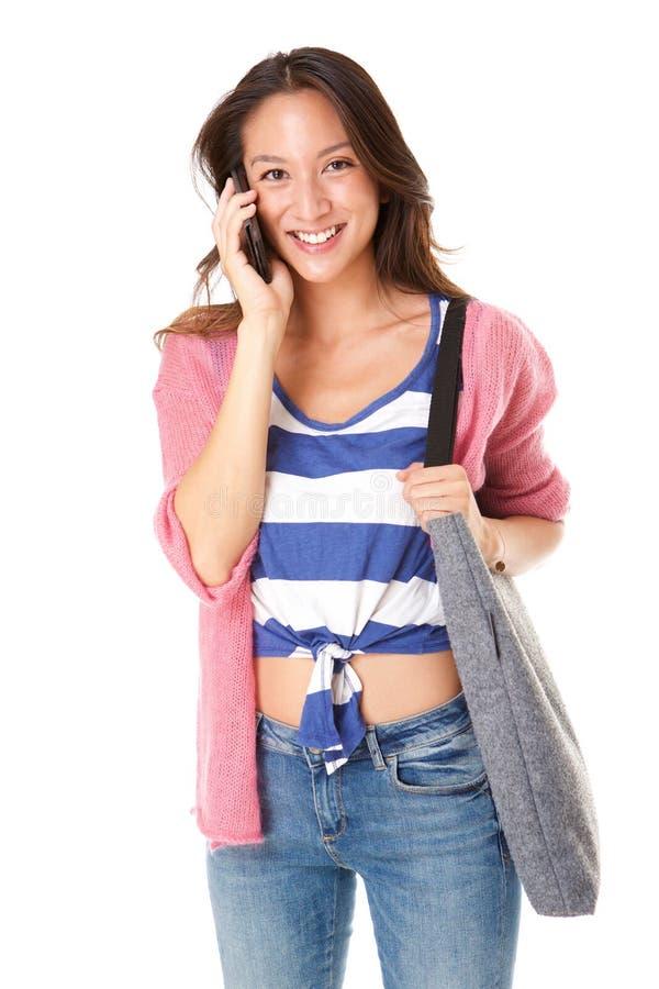 Mulher asiática nova moderna que sorri com bolsa e que fala no telefone esperto foto de stock royalty free