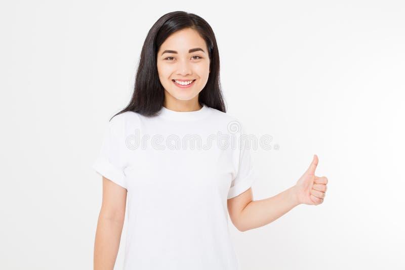 Mulher asiática nova na camisa da placa t do molde que mostra o polegar grande isolado acima no fundo branco Conceito feliz e do  imagens de stock royalty free