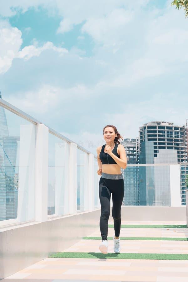 Mulher asiática nova no desgaste do esporte que faz esportes fora foto de stock royalty free