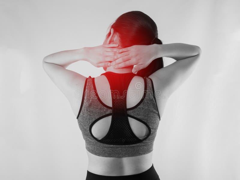 Mulher asiática nova no pano do exercício que tem a dor de pescoço com o ponto vermelho do foco no fundo fotos de stock royalty free