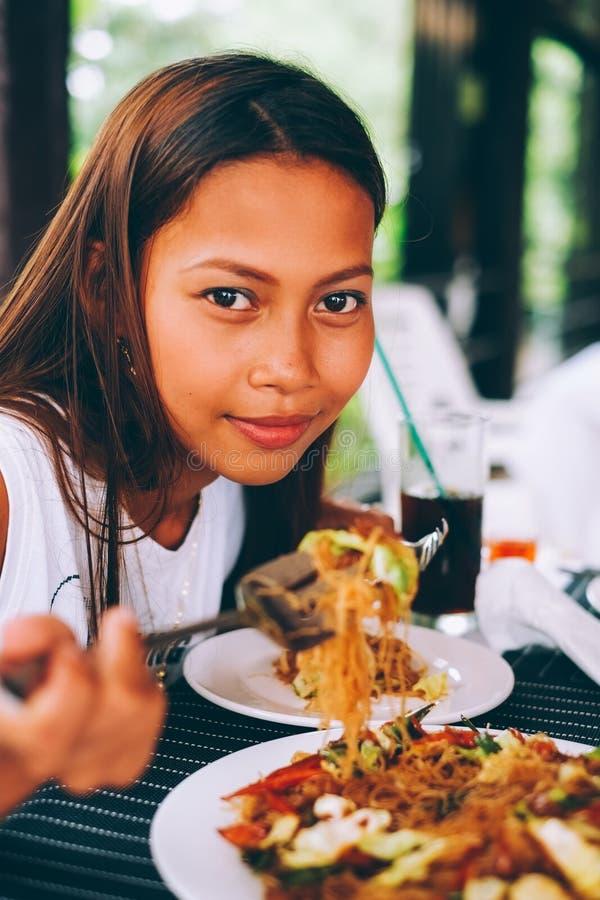 Mulher asiática nova no restaurante que come o macarronete de arroz da fritada da agitação com carne e vegetais, bihon filipino d imagem de stock