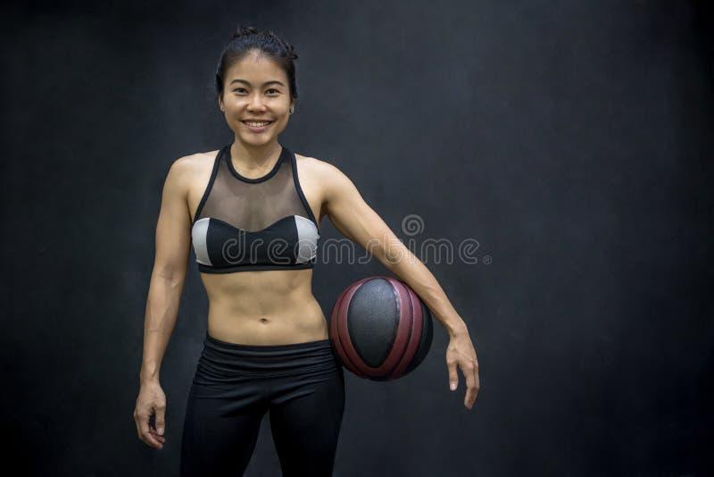 Mulher asiática nova no sportwear que guarda o basquetebol foto de stock royalty free