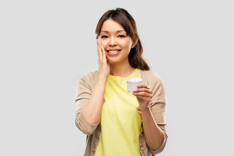 Mulher asiática nova que aplica o creme hidratante a sua cara imagem de stock royalty free