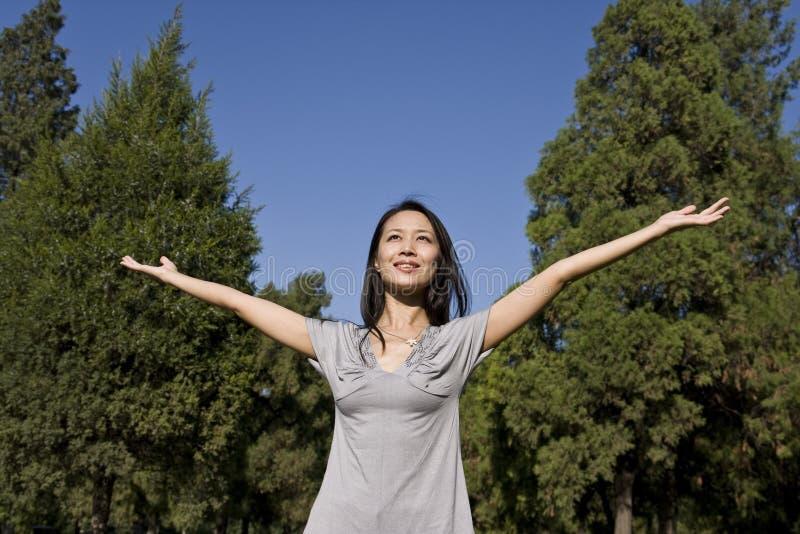 Mulher asiática nova que aprecia a luz solar fotografia de stock