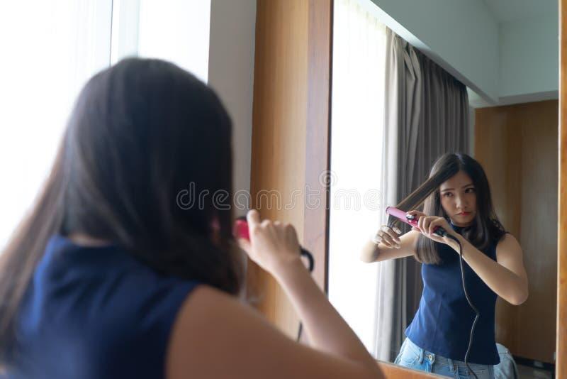 Mulher asiática nova que endireita o cabelo com whil do straightener do cabelo foto de stock royalty free