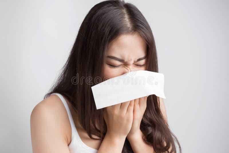 A mulher asiática nova que espirra, trava um frio foto de stock royalty free