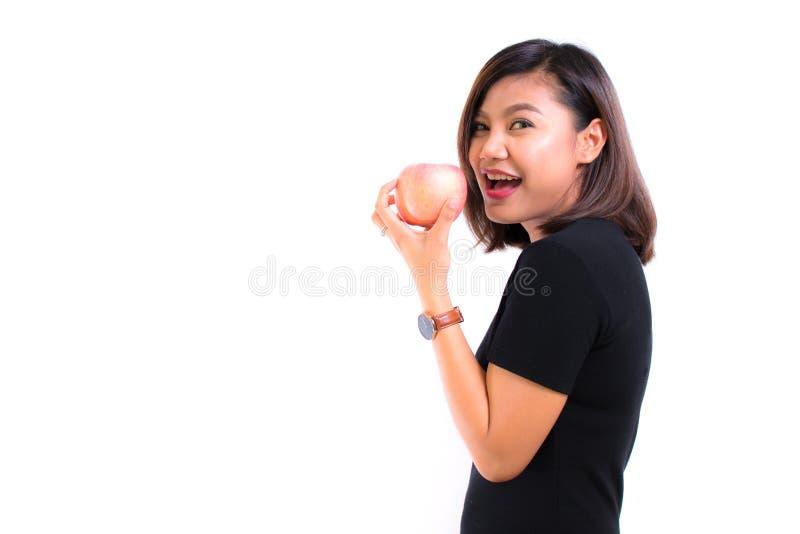 Mulher asiática nova que guarda a maçã vermelha clara no fundo branco P imagem de stock