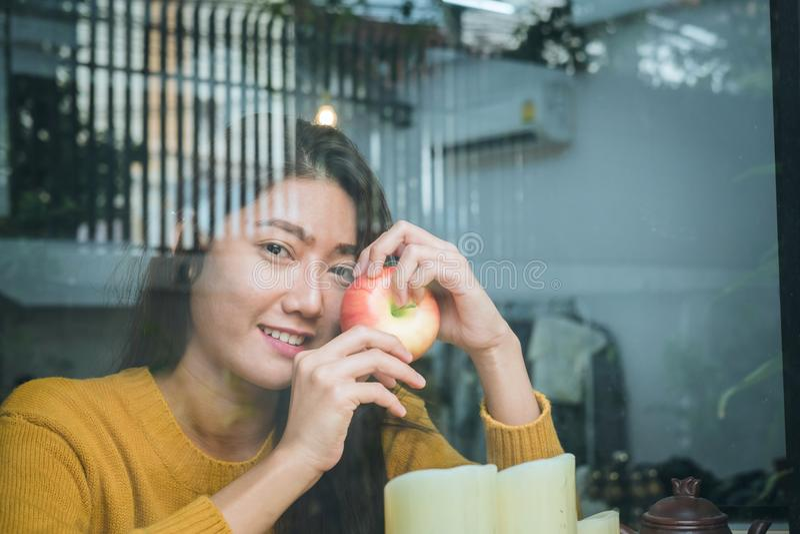 Mulher asiática nova que guarda a maçã vermelha e que olha fora do restauran fotos de stock